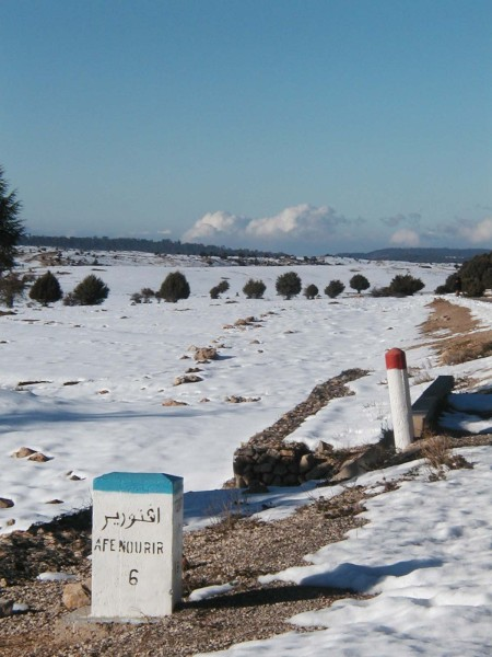 Paysage de neige sans arbre mais avec une borne kilométrique
